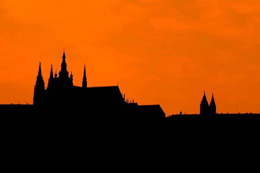 Prahan linnan siluetti auringonlaskua vasten.