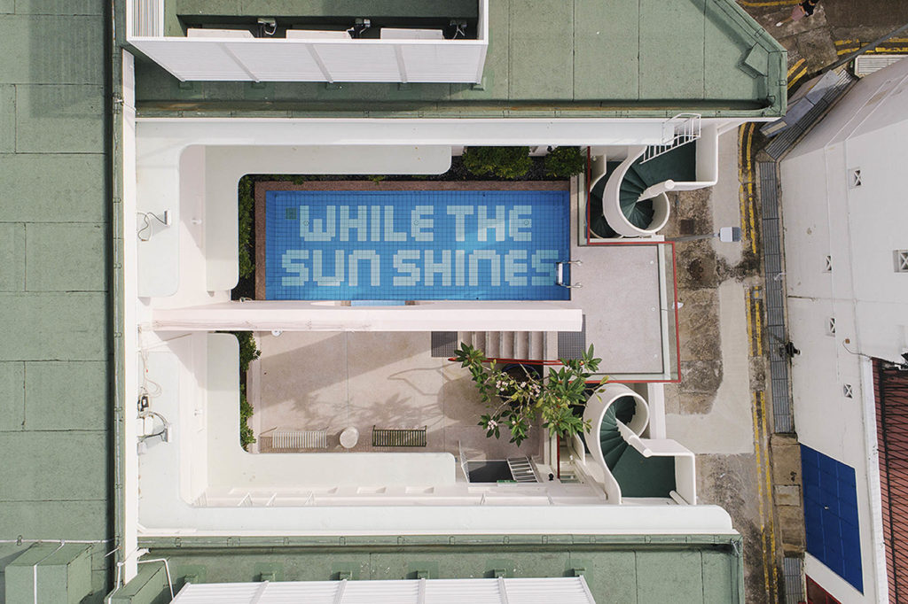 Hotellin uima-allas julistaa sanomaa: While the sun shines!