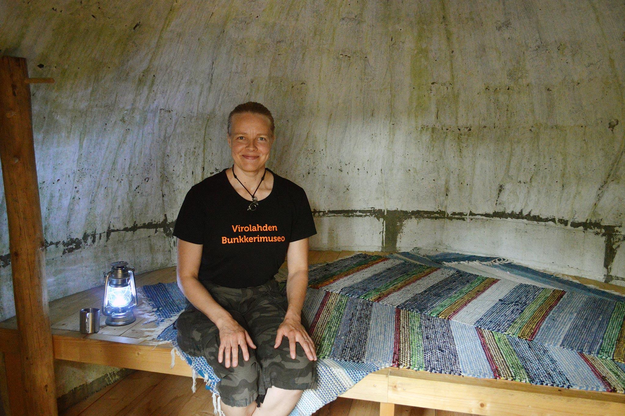 Virolahden Bunkkerimuseon opas Tiia Kimmo istuu pallokorsun puulaverin päällä.